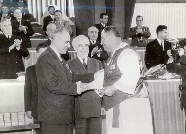 1024px-E395_End_of_collectivization_meeting_medals
